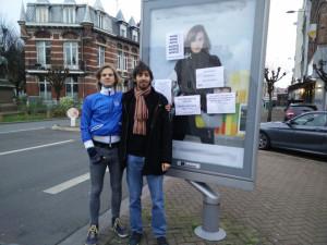 Deux membres de R.A.P. Lille Métropole après avoir recouvert un panneau publicitaire