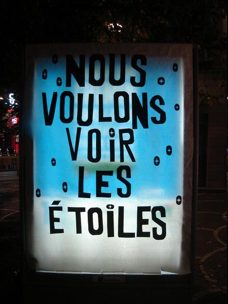"""Panneau publicitaire lumineux recouvert du message """"Nous voulons voir les étoiles"""""""