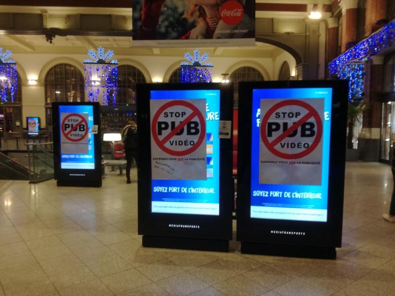 Écrans publicitaires vidéos recouverts avec des affiches dnas une gare SNCF